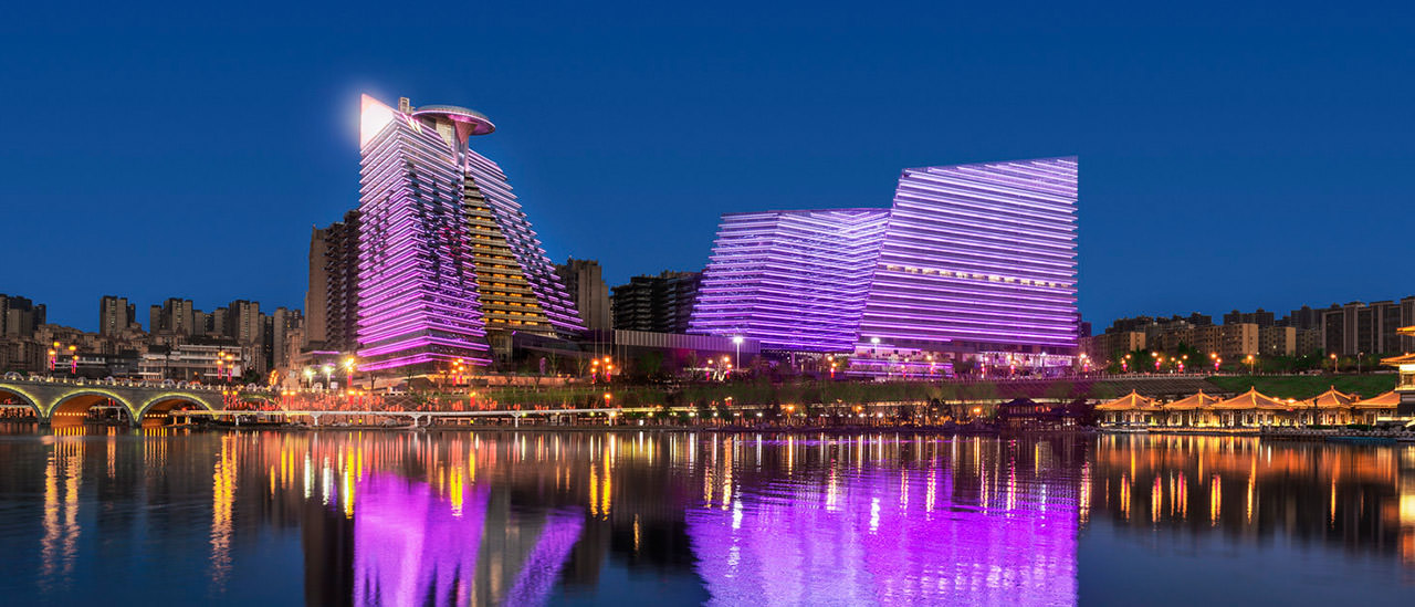Hotel with brilliant purple lighting overlooking shimmering, illuminated water at night